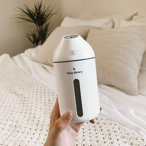 """<h2>Invest In A Bedside-Table Humidifier<br></h2><br>If you do nothing else, get a damn humidifier. <a href=""""https://www.refinery29.com/en-us/best-humidifier-home-reviews"""" rel=""""nofollow noopener"""" target=""""_blank"""" data-ylk=""""slk:They come cute and tiny now"""" class=""""link rapid-noclick-resp"""">They come cute and tiny now</a>. Plus, most dermatologists practicing in states that experience four seasons agree that the dry heat warming your house or apartment is not great for you skin. """"In those heated, low-humidity environments, we lose more moisture from our skin into the air,"""" explains New York-based dermatologist <a href=""""https://bewelltonic.com/dr-king/?gclid=CjwKCAjw2P-KBhByEiwADBYWCgohjIIg_tCz1osUdMA37xW3_iCi2Vnsf4y4ke4htN3ck3ijKZNfZxoCdaYQAvD_BwE"""" rel=""""nofollow noopener"""" target=""""_blank"""" data-ylk=""""slk:Dr. Hadley King."""" class=""""link rapid-noclick-resp"""">Dr. Hadley King.</a> """"A humidifier in the bedroom at night, or in other rooms where you are spending a lot of time, can keep you from getting a scratchy throat or feeling puffy because your skin's dehydrated.""""<br><br><strong>Hey Dewy</strong> Portable Facial Humidifier, $, available at <a href=""""https://go.skimresources.com/?id=30283X879131&url=https%3A%2F%2Fwww.revolve.com%2Fhey-dewy-portable-facial-humidifier-in-pearl%2Fdp%2FHEDY-WU1%2F"""" rel=""""nofollow noopener"""" target=""""_blank"""" data-ylk=""""slk:Revolve"""" class=""""link rapid-noclick-resp"""">Revolve</a>"""