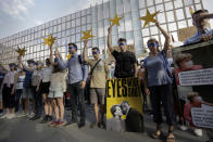 "Protesters hold EU stars and keep their eyes closed behind a poster showing German Chancellor Angela Merkel and Bulgarian Prime Minister Boyko Borissov in front of the German Embassy in Sofia, Bulgaria, Wednesday, Aug. 12, 2020. Several hundred anti-government protesters gathered in front of Germany's embassy in Sofia, calling on Berlin and Brussels to ""open their eyes"" to widespread corruption in Bulgaria. During the peaceful protest, dubbed ""Eyes Wide Shut,"" organizers complained that the European Union has willfully ignored the state of affairs in its poorest member state. (AP Photo/Valentina Petrova)"