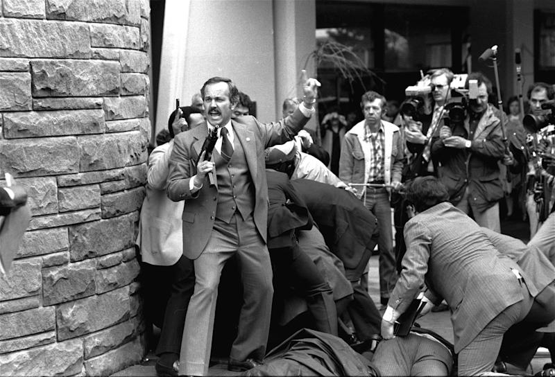 FILE - In this Monday, March 30, 1981 file photo, a Secret Service agent, automatic weapon drawn, yells orders after shots were fired at President Ronald Reagan outside a hotel in Washington. The Secret Service has been tarnished by a prostitution scandal that erupted April 13, 2012 in Colombia involving 12 Secret Service agents, officers and supervisors and 12 more enlisted military personnel ahead of President Barack Obama's visit there for the Summit of the Americas. (AP Photo/Ron Edmonds)