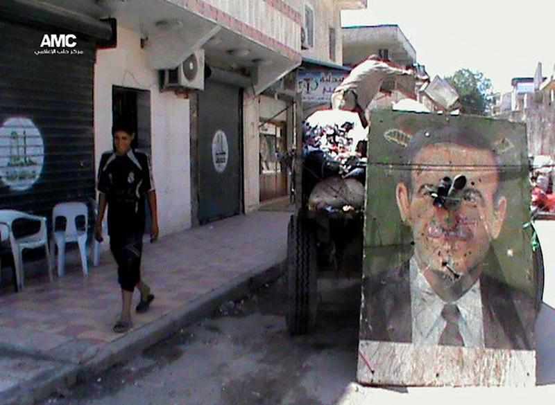 This citizen journalism image provided by Aleppo Media Center AMC which has been authenticated based on its contents and other AP reporting, shows a poster of late Syrian President Hafez Assad on a garbage truck, in Aleppo, Syria, Thursday, June 6, 2013. Syrian troops and their Lebanese Hezbollah allies captured a strategic border town Wednesday after a grueling three-week battle, dealing a severe blow to rebels and opening the door for President Bashar Assad's regime to seize back the country's central heartland. The regime triumph in Qusair, which Assad's forces had bombarded for months without success, demonstrates the potentially game-changing role of Hezbollah in Syria's civil war. (AP Photo/Aleppo Media Center AMC)