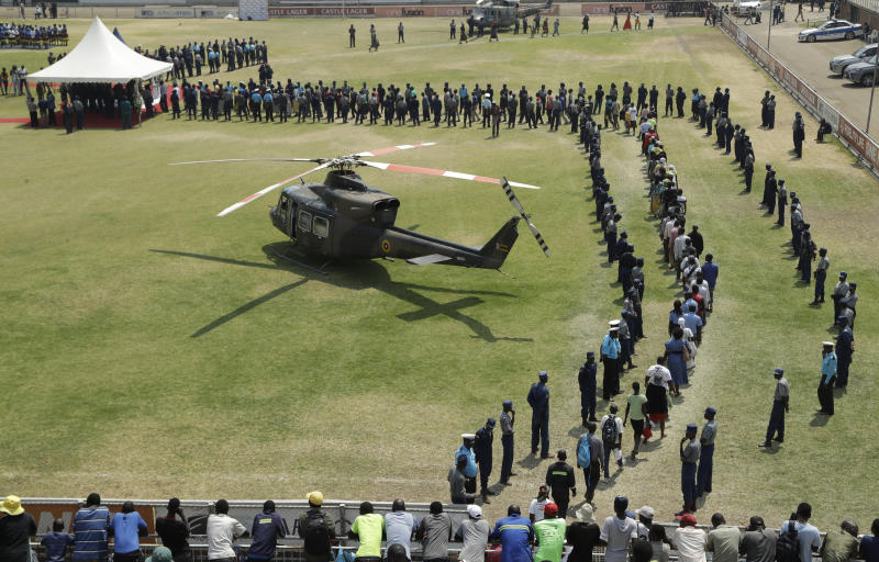 A helicopter carrying the coffin of former Zimbabwean President Robert Mugabe lands at the Rufaro Stadium in Harare, Friday, Sept. 13, 2019, where the body is on view at the stadium for a second day. Mugabe died last week in Singapore at the age of 95. He led the southern African nation for 37 years before being forced to resign in late 2017. (AP Photo/Themba Hadebe)