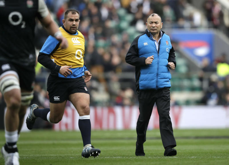 FILE - In this Saturday, March 9, 2019, file photo, England head coach Eddie Jones, right, watches his players warm up ahead of their Six Nations rugby union international match against Italy at Twickenham stadium in London. England has had wild fortunes this Rugby World Cup cycle under Eddie Jones but appears to be running into good form ahead of the tournament in Japan. (AP Photo/Matt Dunham, File)