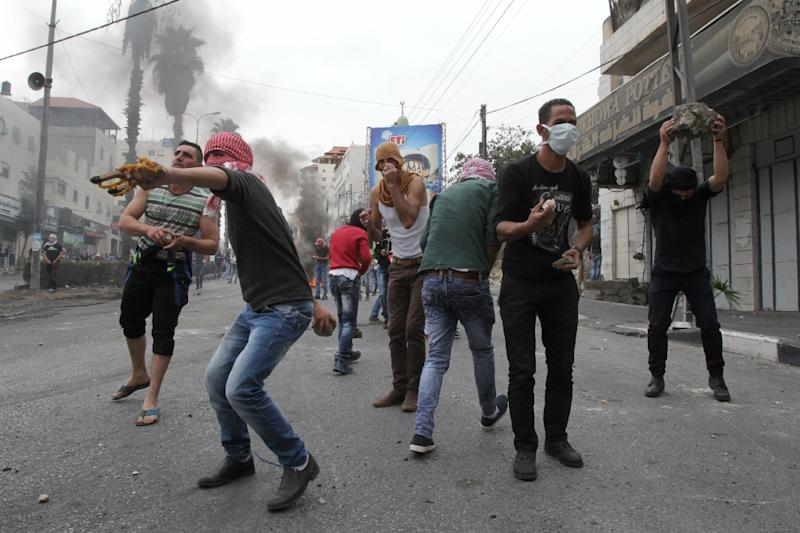 Palestinian stone throwers clash with Israeli security forces following Friday prayers on October 23, 2015, in the West Bank town of Hebron (AFP Photo/Hazem Bader)