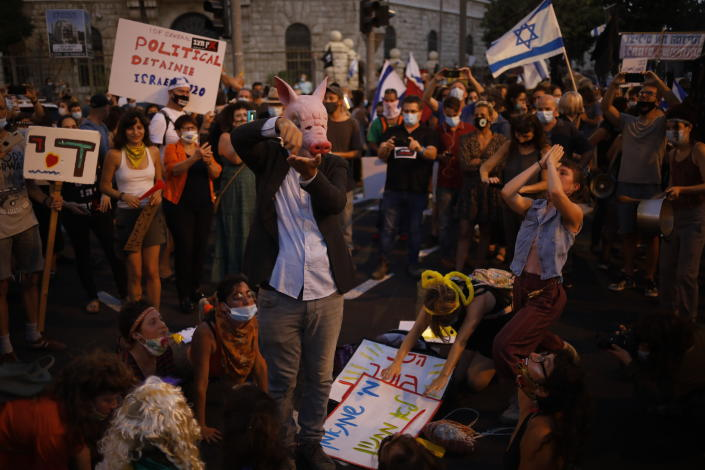 Demonstrators, defying orders to maintain social distancing requirements, chant slogans and blow horns outside Prime Minister's residence in Jerusalem, Tuesday, July 14, 2020. Thousands of Israelis demonstrated outside of the official residence of Benjamin Netanyahu, calling on the embattled Israeli leader to resign as he faces a trial on corruption charges and grapples with a deepening coronavirus crisis. (AP Photo/Ariel Schalit)