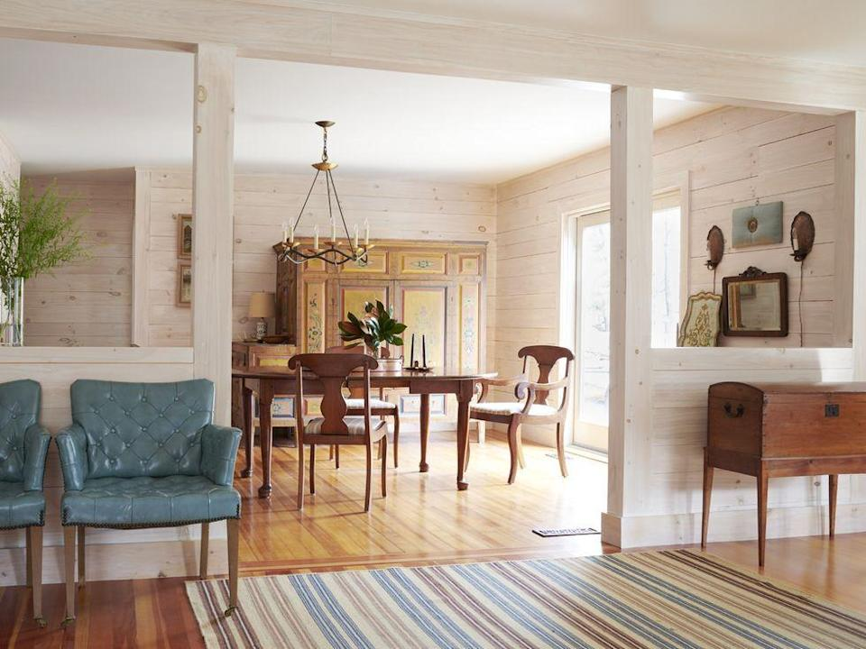 """<p>The ground floor in ELLE DECOR visual director David Murphy's <a href=""""https://www.elledecor.com/design-decorate/house-interiors/a36532576/david-murphy-berkshires-home/"""" rel=""""nofollow noopener"""" target=""""_blank"""" data-ylk=""""slk:Columbia County, New York, retreat"""" class=""""link rapid-noclick-resp"""">Columbia County, New York, retreat</a> incorporates fall hues throughout. In the dining area, pops of a muted blue on the chairs and rug complement the the sand-toned shiplap walls and wood furniture.</p>"""