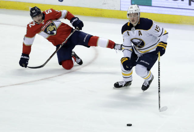 Buffalo Sabres' Jack Eichel (15) goes for the puck as Florida Panthers' MacKenzie Weegar (52) falls to the ice during the second period of an NHL hockey game, Saturday, April 7, 2018, in Sunrise, Fla. (AP Photo/Lynne Sladky)