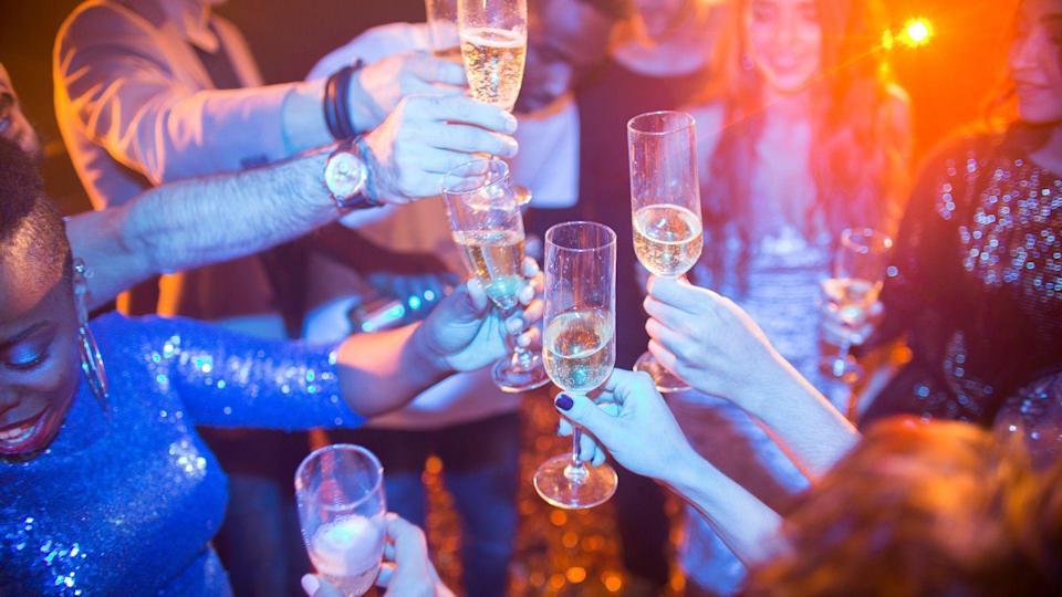 High angle view at multi-ethnic group of laughing young people enjoying dance party in nightclub and drinking champagne, focus on clinking glasses.