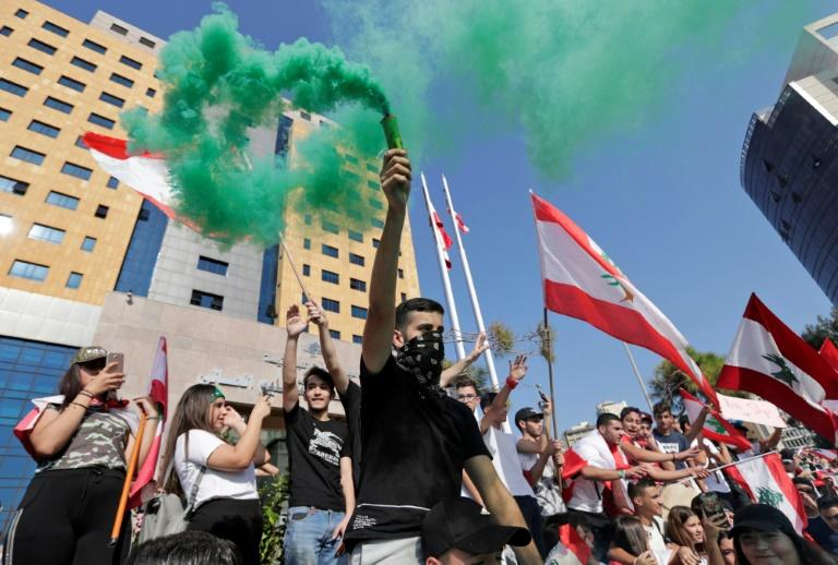 Lebanese school students wave the national flag and flares as they protest outside the education ministry in Beirut (AFP Photo/ANWAR AMRO)