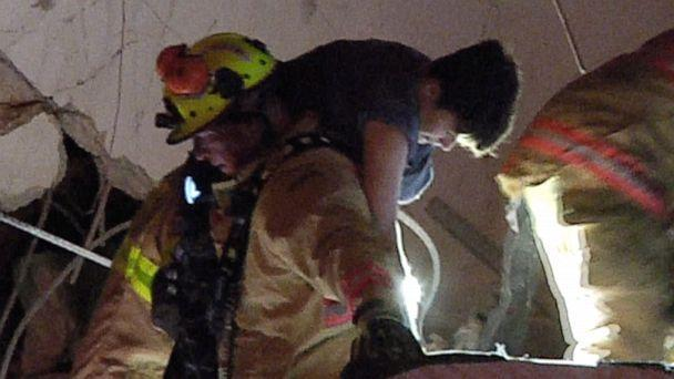 PHOTO: In an image made from video provided by ReliableNewsMedia, firefighters rescue a survivor from the rubble of the Champlain Towers South Condo after the multistory building partially collapsed in Surfside, Fla., early Thursday, June 24, 2021. (ReliableNewsMedia via AP)