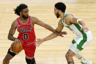 Chicago Bulls guard Coby White, left, drives against Boston Celtics forward Jayson Tatum during the second half of an NBA basketball game in Chicago, Friday, May 7, 2021. (AP Photo/Nam Y. Huh)