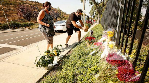 PHOTO: Lorraine Maralian and her son Anthony Maralian of Westlake Village place flowers and pray at a growing memorial for two brothers who were fatally injured while crossing  Triunfo Canyon Road, Westlake Village, Calif., Sept. 30, 2020. (Al Seib/Los Angeles Times via Getty Imag)