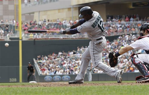 Seattle Mariners' Trayvon Robinson hits a two-run single off Minnesota Twins pitcher Casey Fien during the sixth inning of a baseball game, Thursday, Aug. 30, 2012, in Minneapolis. Catching is Twins' Joe Mauer. (AP Photo/Jim Mone)