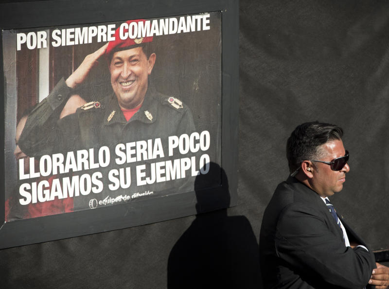 """A security officer stands guard near a poster of late Venezuelan President Hugo Chavez that reads in Spanish """"forever commander, crying for him is not enough, let's follow his example"""", at mass at the Villa 21 slum in Buenos Aires, Argentina, Wednesday, March 5, 2014. Argentine President Cristina Fernandez attended the mass in honor of Chavez, one year after the Venezuelan leader's death. (AP Photo/Victor R. Caivano)"""