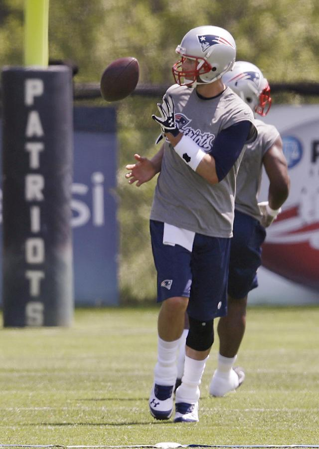 New England Patriots quarterback Tom Brady (12) catches a ball during an organized team activity at the NFL football team's facility Friday, May 30, 2014 in Foxborough, Mass. (AP Photo/Stephan Savoia)