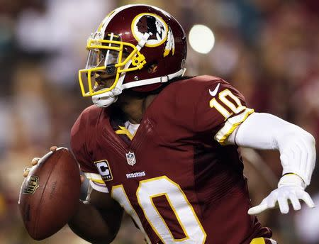 Redskins' Griffin III scrambles against the Eagles' defense during the second half of their NFL football game in Landover in this file photo