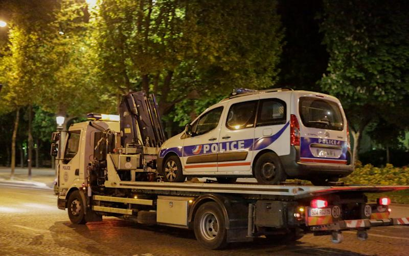 A police van is towed away from the Champs-Elysees following the shooting - Credit: Barcroft