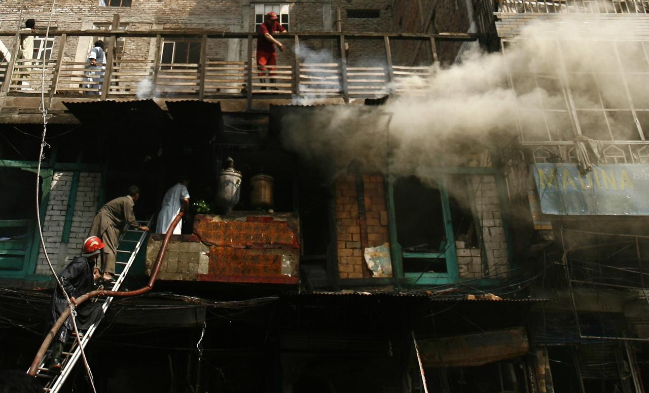 Smoke rises from the building as firefighters work to extinguish the fire at the site of a bomb attack in Peshawar September 29, 2013. Twin blasts in the northwestern Pakistan city of Peshawar killed 33 people and wounded 70 on Sunday, a week after two bombings at a church in the frontier city killed scores, police and hospital authorities said.REUTERS/Khuram Parvez (PAKISTAN - Tags: POLITICS CIVIL UNREST CRIME LAW)
