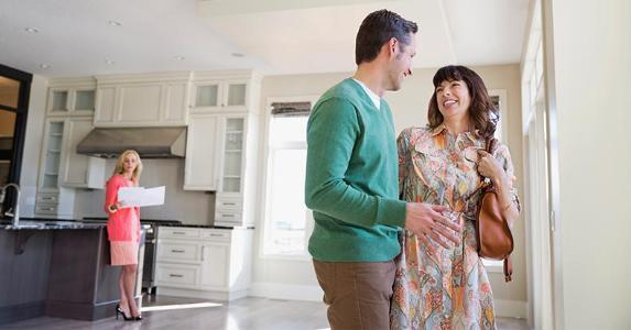 Couple discussing potential house purchase with agent on background | Hero Images/Getty Images