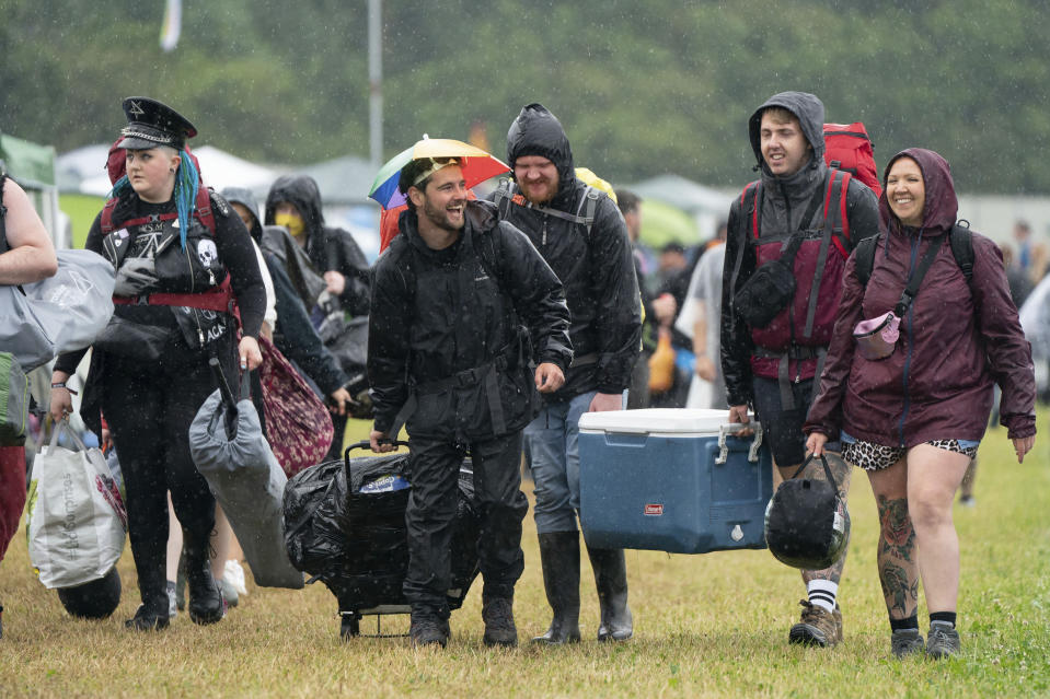 Festivalgoers arrive during a downpour on the first day of Download Festival at Donington Park at Castle Donington, England, Friday June 18, 2021. The three-day music and arts festival is being held as a test event to examine how Covid-19 transmission takes place in crowds, with the the capacity significantly reduced from the normal numbers. (Joe Giddens/PA via AP)