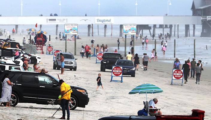 Families and young adults play on the beach near the pier on March 23, 2021, in Daytona Beach, Fla.