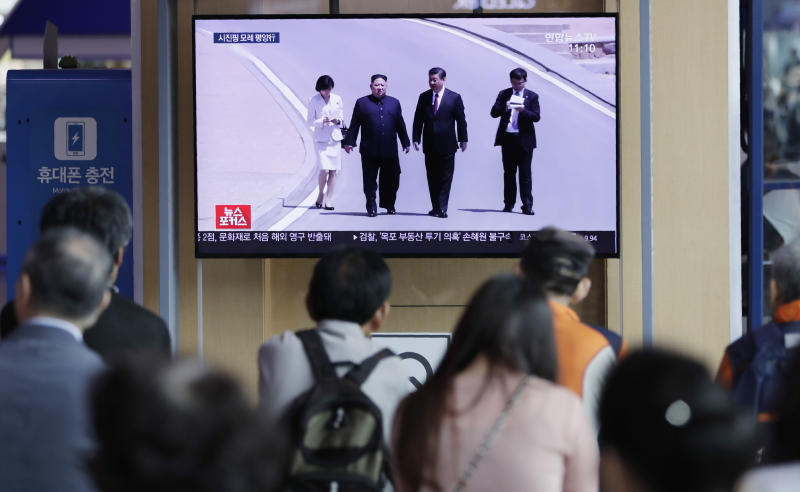 "People watch a TV news program reporting about Chinese President Xi Jinping's state visit to North Korea with file footage of Xi and North Korean leader Kim Jong Un, at the Seoul Railway Station in Seoul, South Korea, Tuesday, June 18, 2019. The letters on the top read ""Chinese President Xi Jinping will visit Pyongyang on June 20"". (AP Photo/Lee Jin-man)"