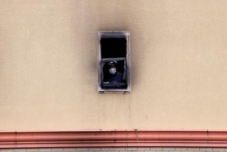 A firefighter looks out of a window at the torched Kyoto Animation building in Kyoto