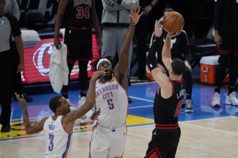 Chicago Bulls guard Zach LaVine (8) attempts a 3-point shot over Oklahoma City Thunder guard George Hill (3) and forward Luguentz Dort (5), but misses in the closing seconds of overtime of an NBA basketball game Friday, Jan. 15, 2021, in Oklahoma City. (AP Photo/Sue Ogrocki)
