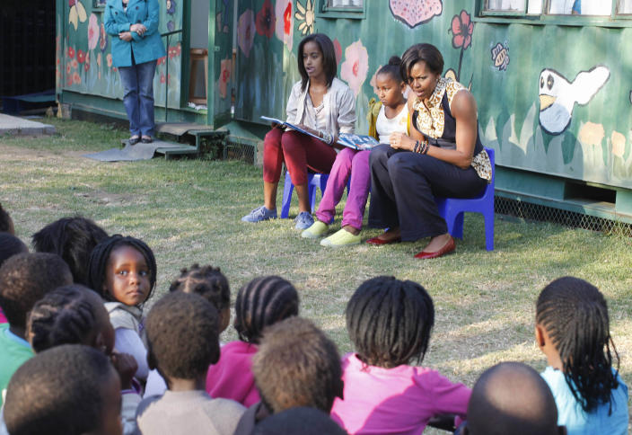 """FILE - In this June 21, 2011, file photo, first lady Michelle Obama, with daughters Malia, left, and Sasha, center, read from """"The Cat in the Hat,"""" by Dr. Seuss, during their visit to the Emthonjeni Community Center in Zandspruit Township, Johannesburg, South Africa. Michelle Obama has a new look, both in person and online, and with the president's re-election, she has four more years as first lady, too. The first lady is trying to figure out what comes next for this self-described """"mom in chief"""" who also is a champion of healthier eating, an advocate for military families, a fitness buff and the best-selling author of a book about her White House garden. For certain, she'll press ahead with her well-publicized efforts to reduce childhood obesity and rally the country around its service members. (AP Photo/Charles Dharapak, Pool, file)"""