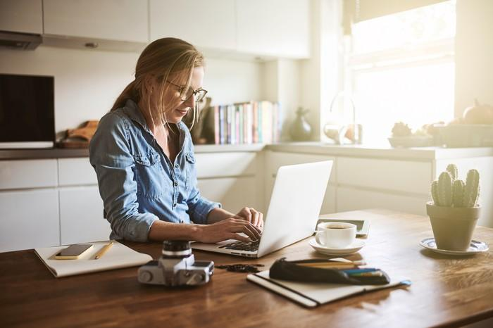 Woman typing on laptop in home kitchen