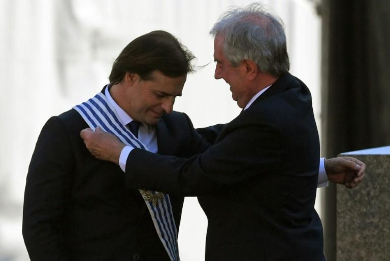 Uruguay's outgoing president Tabare Vazquez places the presidential sash on incoming leader Luis Lacalle Pou (AFP Photo/EITAN ABRAMOVICH)
