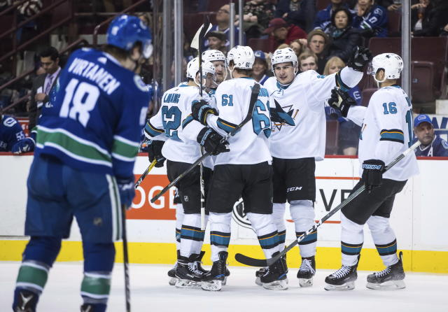 San Jose Sharks' Kevin Labanc; Paul Martin; Justin Braun; Timo Meier, of Switzerland; and Eric Fehr, from left, celebrate Meier's goal as Vancouver Canucks' Jake Virtanen, front left, skates to the bench during the third period of an NHL hockey game Saturday, March 17, 2018, in Vancouver, British Columbia. (Darryl Dyck/The Canadian Press via AP)