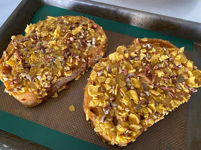 Two slices of uncooked French toast topped with cornflakes and pecans on a baking sheet