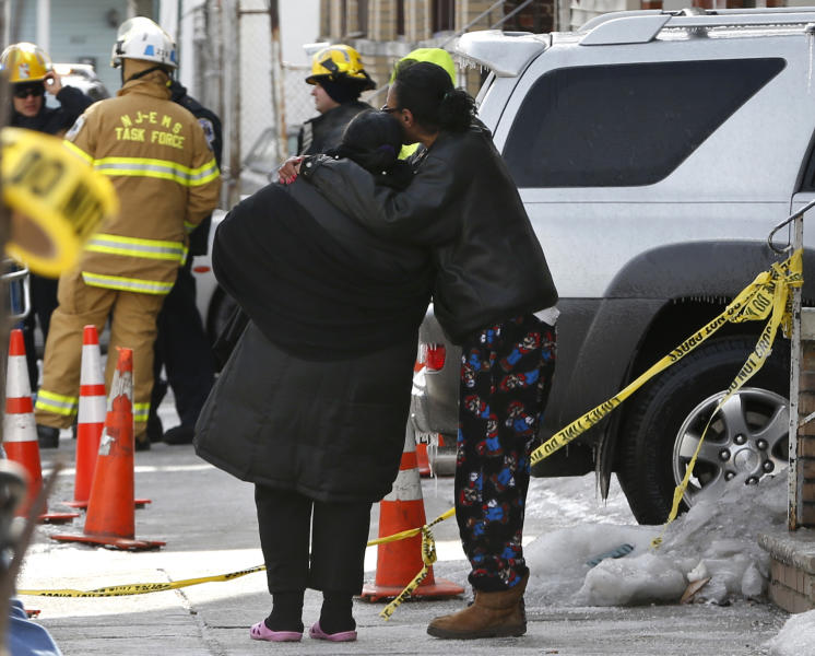 A woman is consoled by another woman near the scene of a four-alarm fire in Jersey City, N.J. on Thursday, March 6, 2014. Mayor Steven Fulop said a couple in their 80s and their two sons, who are in their 50s, were unaccounted for after the blaze on Grant Avenue was extinguished early Thursday. Authorities have not identified the two bodies that were found in the charred home. (AP Photo/Julio Cortez)