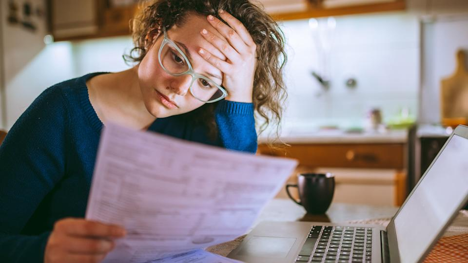 Young brunette curly female reading her bill papers, looking stressed.