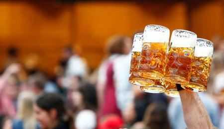 FILE PHOTO: A waiter carries glasses of beer during the opening day of the 184th Oktoberfest in Munich, Germany, September 16, 2017. REUTERS/Michaela Rehle/File Photo