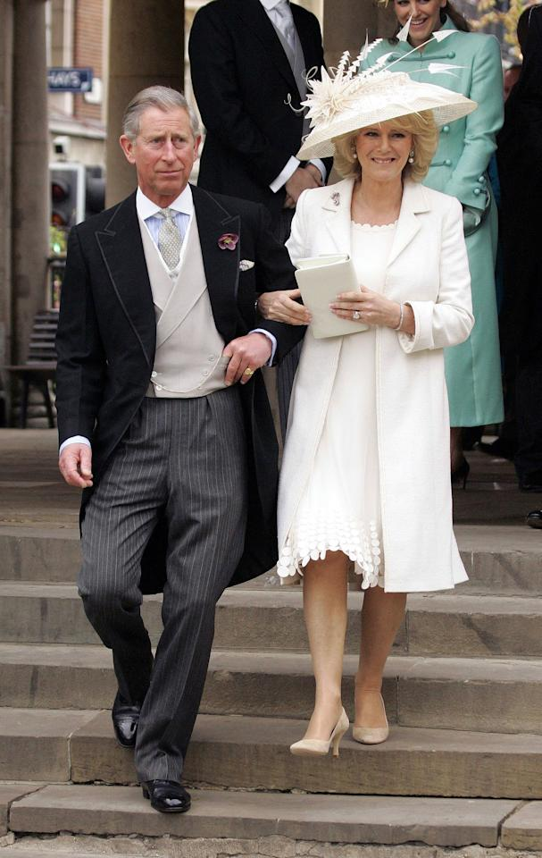 Camilla's wedding dress for the first ceremony was a white silk chiffon dress, which she paired with a matching coat. She completed the outfit with a wide-brimmed hat by Philip Treacy, decorated with elaborate feathers.