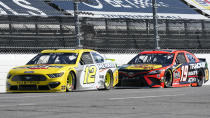 Ryan Blaney (12) and Martin Truex Jr. (19) approach the third turn during a NASCAR Cup Series auto race at Martinsville Speedway in Martinsville, Va., Sunday, April 11, 2021. (AP Photo/Steve Helber)