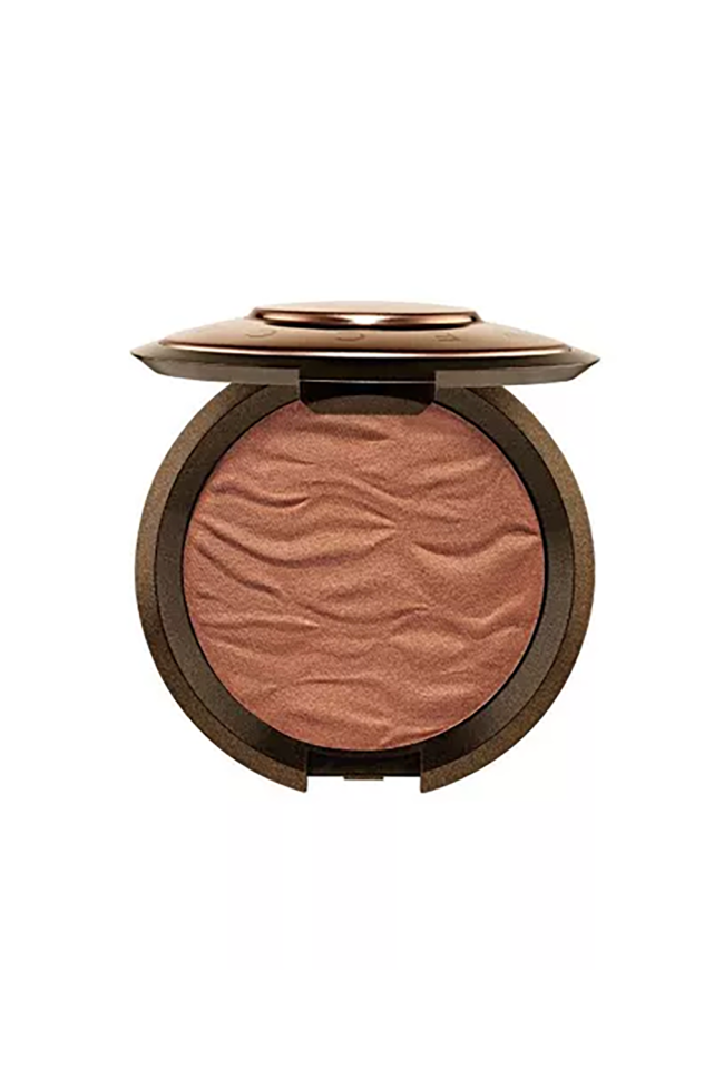 """<p><strong>Becca</strong></p><p>sephora.com</p><p><strong>$38.00</strong></p><p><a href=""""https://go.redirectingat.com?id=74968X1596630&url=https%3A%2F%2Fwww.sephora.com%2Fproduct%2Fsunlit-bronzer-P419604&sref=http%3A%2F%2Fwww.marieclaire.com%2Fbeauty%2Fmakeup%2Fg4879%2Fbest-self-tanners-bronzers-dark-skin%2F"""" target=""""_blank"""">SHOP IT</a></p><p>Counting down the days until you can be on a beach again? Well, this bronzer was inspired by """"sun-drenched destinations""""—so, basically it's a vacation must-have you need. With the help of super finely-milled pigments, this blendable bronzer imparts the most gorgeous glow on dark skin tones. </p>"""