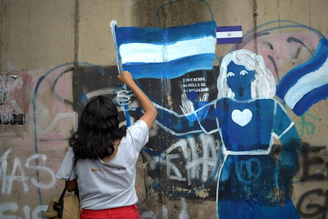 <p>A woman takes part in a vigil to commemorate 100 days of protests against the government of Nicaragua's president Daniel Ortega in front of a mural, in Managua on July 26, 2018. (Photo: Marvin Recinos/AFP/Getty Images) </p>