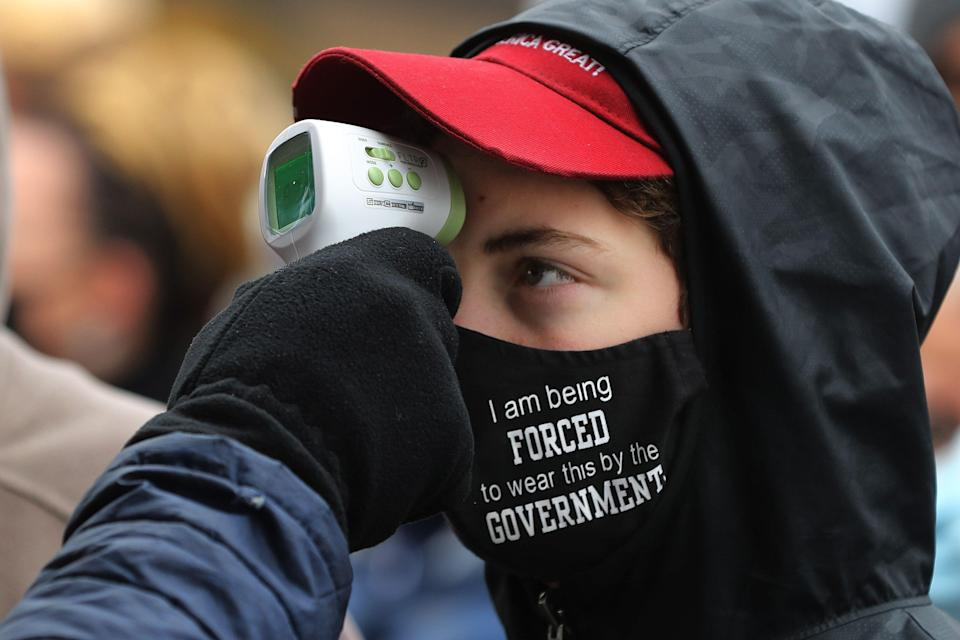 Supporters of President Donald Trump have their temperature taken as a precaution against the coronavirus before attending a campaign rally at Capital Region International Airport Oct. 27 in Lansing, Michigan. (Chip Somodevilla via Getty Images)