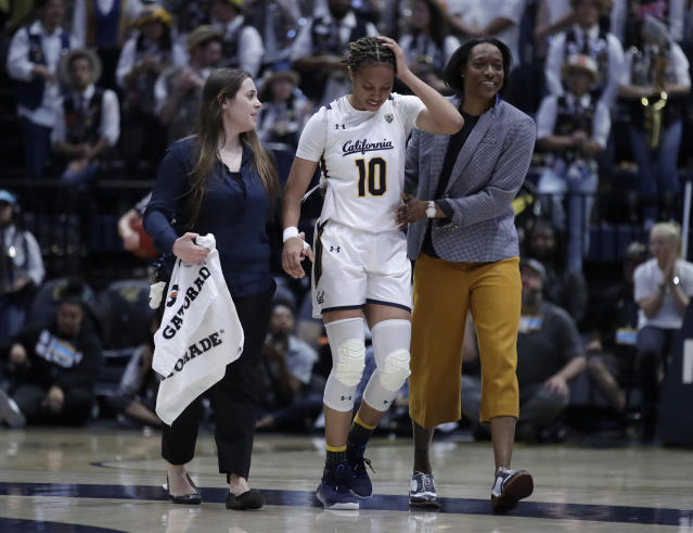 California's Jazlen Green (10) is assisted off the court by coach Charmin Smith, right, and a trainer in the first half of an NCAA college basketball game against Stanford, Sunday, Jan. 12, 2020, in Berkeley, Calif. (AP Photo/Ben Margot)