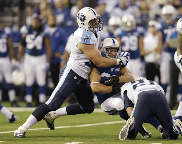 Indianapolis Colts' Donald Brown, center, is tackled by Tennessee Titans' Karl Klug (97) and George Wilson (21) during the first half of an NFL football game Sunday, Dec. 1, 2013, in Indianapolis. (AP Photo/Michael Conroy)