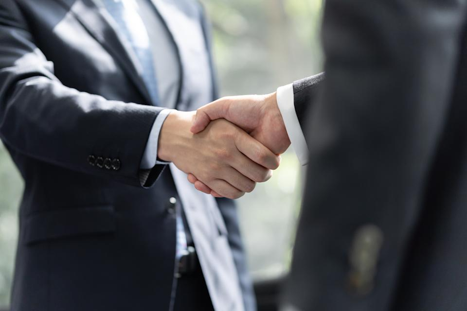 Japanese male businessmen shake hands with each other