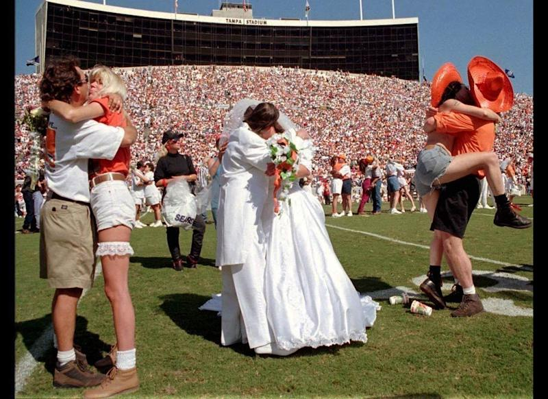 What better way to tackle marriage head-on than to get hitched during a football game? On Oct. 22, 1995, a mass wedding was held for 200 couples during halftime of a game between the Tampa Bay Buccaneers and the Atlanta Falcons. Billed as the largest wedding in NFL history, the couples wore anything and everything to their big day -- from traditional formal wedding attire to more casual garments such as cut-off jean shorts and sombreros.