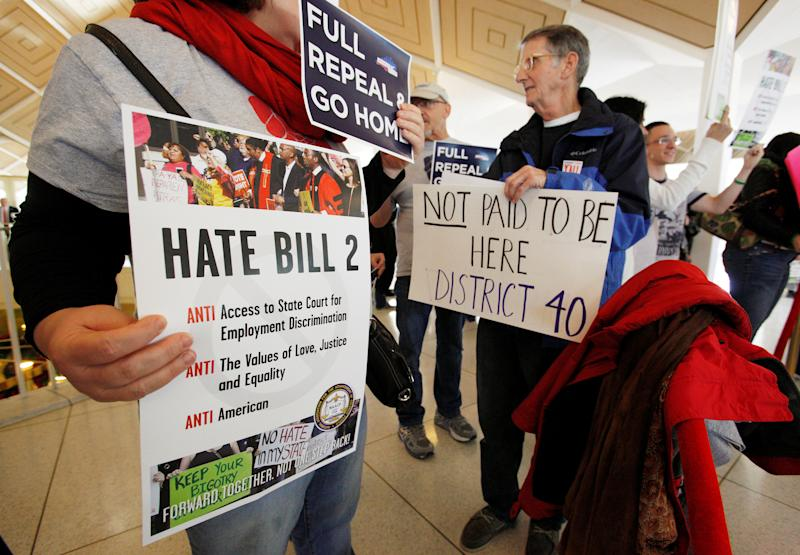 FILE PHOTO - Opponents of North Carolina's HB2 law limiting bathroom access for transgender people protest in the gallery above the state's House of Representatives chamber as the legislature considers repealing the controversial law in Raleigh, North Carolina, U.S. on December 21, 2016. REUTERS/Jonathan Drake/File Photo