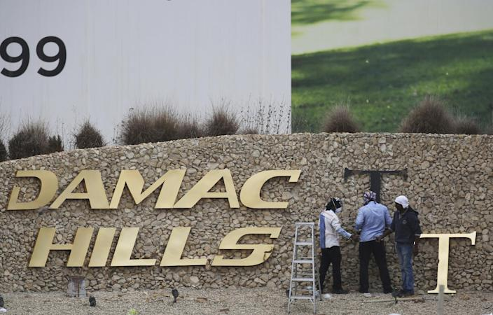 FILE- In this Sunday, Feb. 12, 2017 file photo, workers re-install a gold letter sign for the Trump International Golf Club in Dubai, United Arab Emirates. U.S. President Donald Trump's two sons in charge of his business empire will attend a closed-door event to mark the opening of the Trump International Golf Club in Dubai. (AP Photo/Jon Gambrell, File)