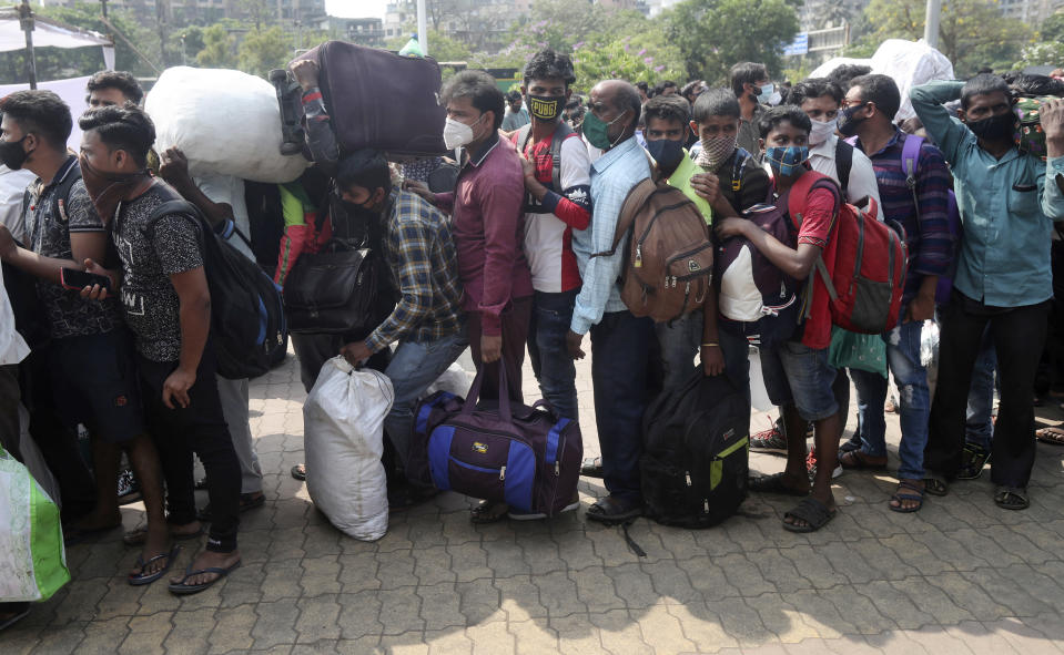 People wearing masks stand in a queue for a train at Lokmanya Tilak Terminus in Mumbai, India, Sunday, April 11, 2021. India is reporting a surge in infections, which according to experts is due in part to growing disregard for social distancing and mask-wearing in public spaces. (AP Photo/Rafiq Maqbool)