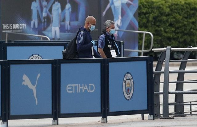 Pep Guardiola arrives at the Etihad Stadium in a mask as football resumed after the coronavirus pandemic