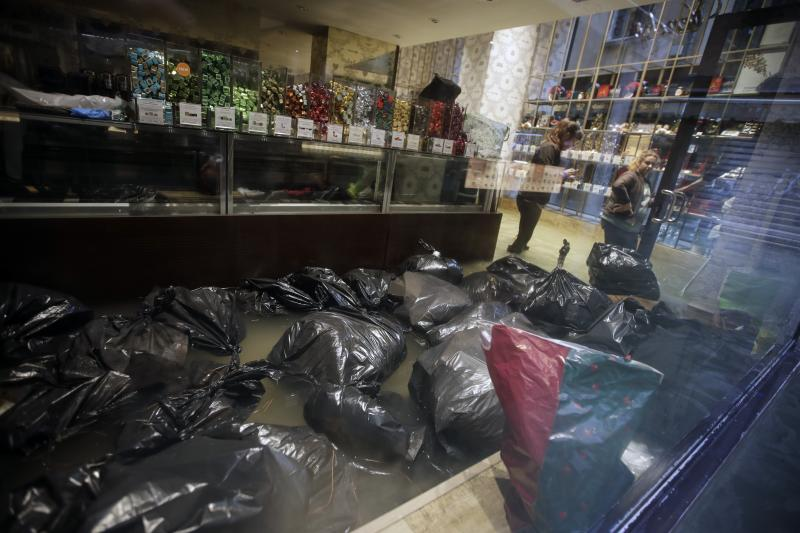 Garbage bags float inside a shop Venice, Italy, Friday, Nov. 15, 2019. Waters are rising in Venice where the tide is reaching exceptional levels just three days after the Italian lagoon city experienced its worst flooding in more than 50 years. (AP Photo/Luca Bruno)