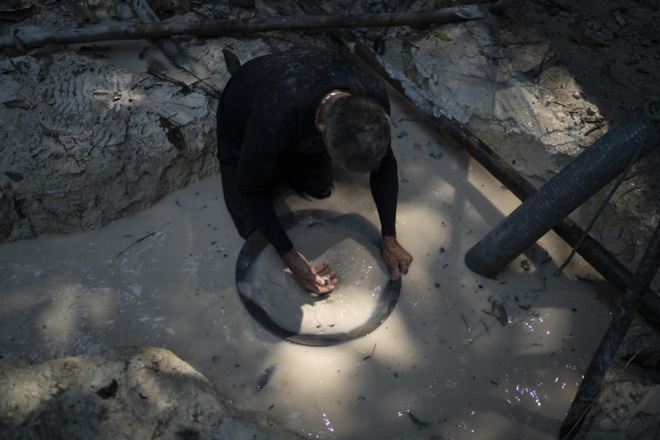 FILE - In this Aug. 21, 2020 file photo, a gold miner uses a pan to separate gold fragments from dirt using water at an illegal mine in the Amazon jungle, in the Itaituba area of Para state, Brazil. Hundreds of wildcat miners attacked police who were trying to halt illegal mining in the Brazilian Amazon region on Wednesday, May 26, 2021 and then the miners raided an Indigenous village, setting houses on fire, federal prosecutors in the northern state of Para reported. (AP Photo/Lucas Dumphreys, File)